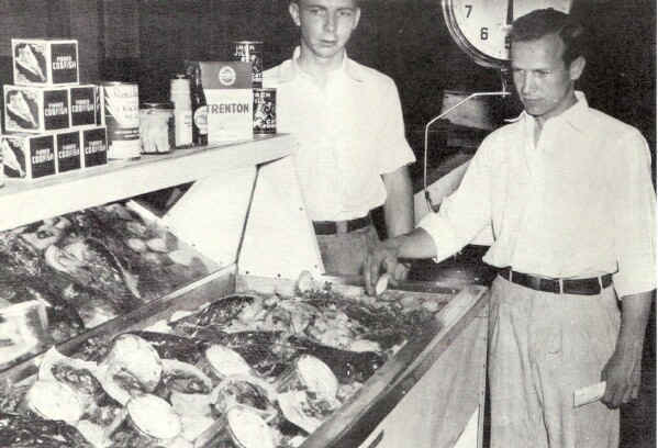 R. W. and H. Stanley Goff inspect a display to tempt the appetites of sea food lovers.; Photo from The Delaware County Advocate, July 1942