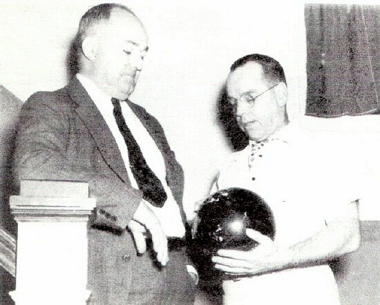 Just looking the situation over - League Secretary Edward Downey examines the ball Howard McCray, President of General Steel's A. A., rolled down the alley in the opening spin. Whether McCray knocked' em all flat in the first trial is quite a different matter.; Photo from The Delaware County Advocate, October 1940
